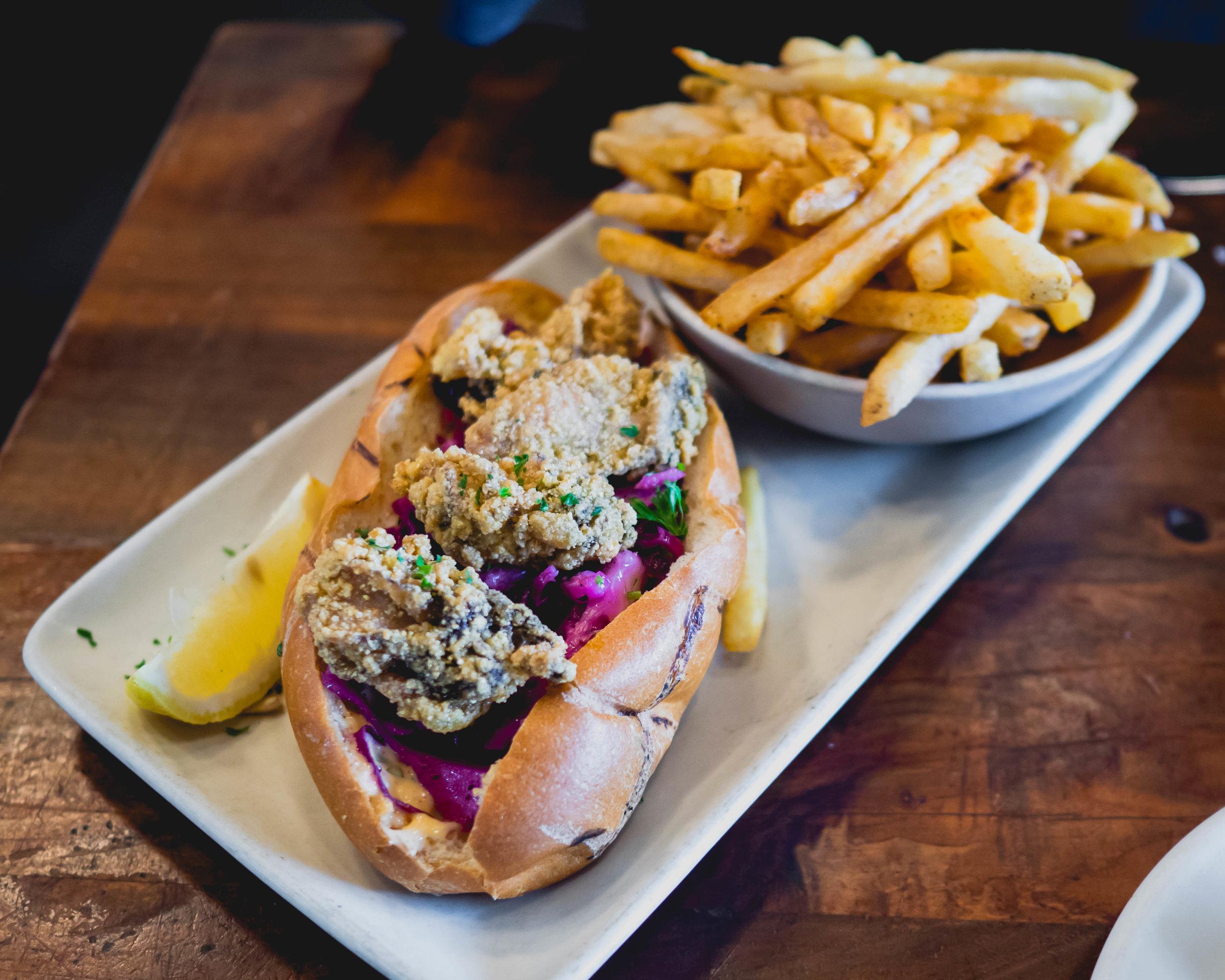 oyster po' boy sandwich : cornmeal fried oysters, hogwash slaw, remoulade, old bay fries.