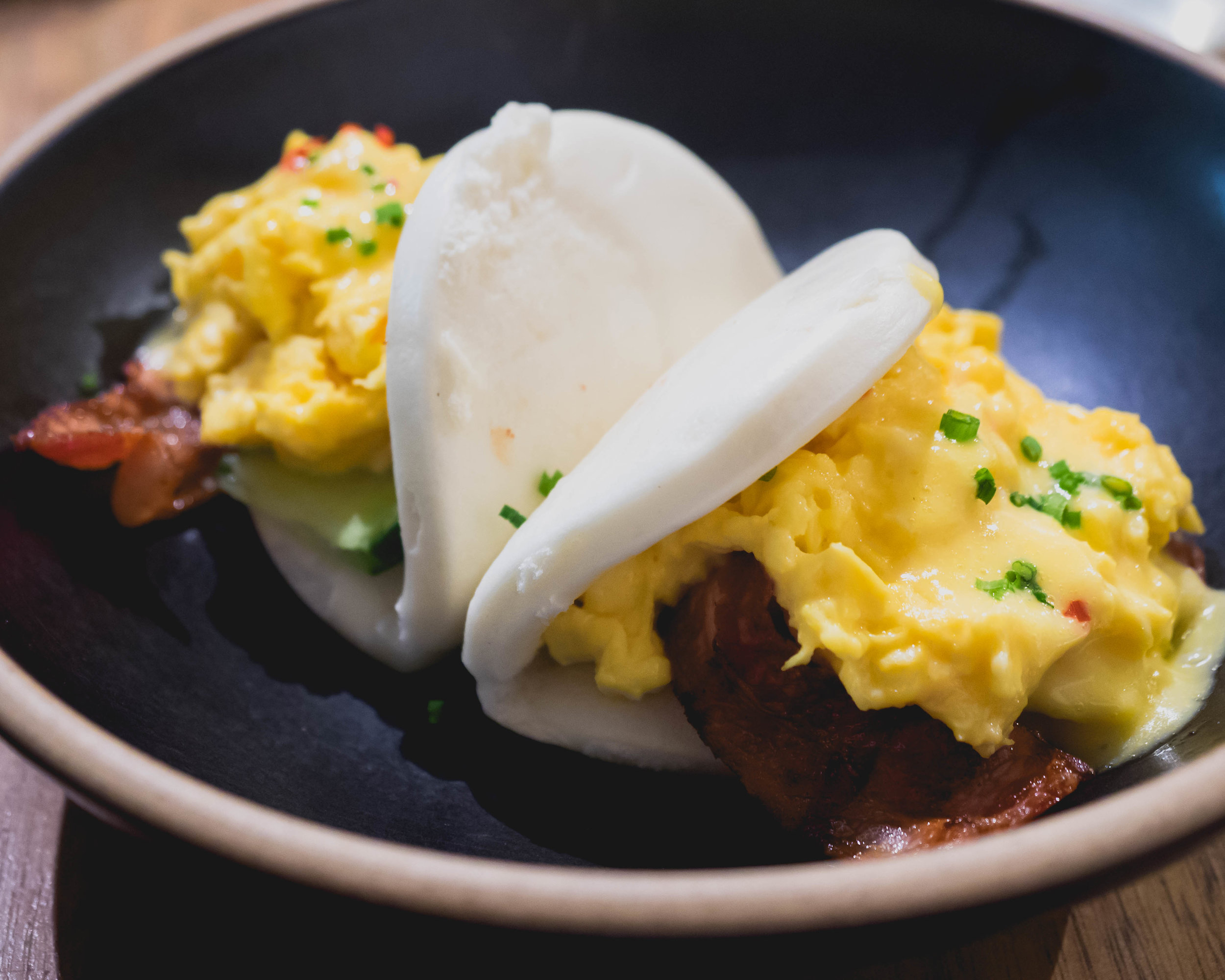 brekkie bao : chilli chives scrambled egg, bacon, cucumber, tomato relish, miso hollandaise.