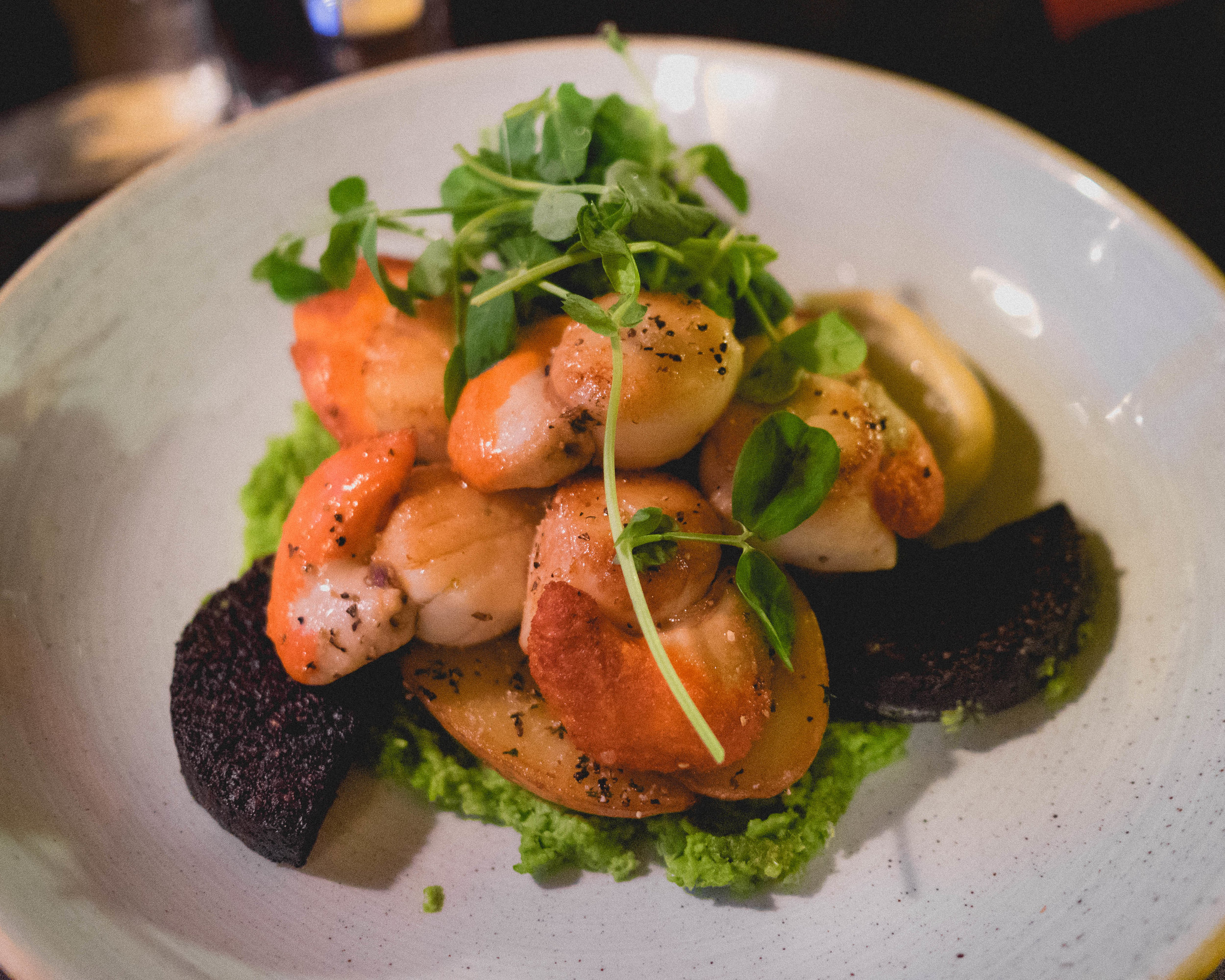 island pan fried scallops  served atop stornoway black pudding, garden pea puree, bacon crumble and sauteed potatoes.