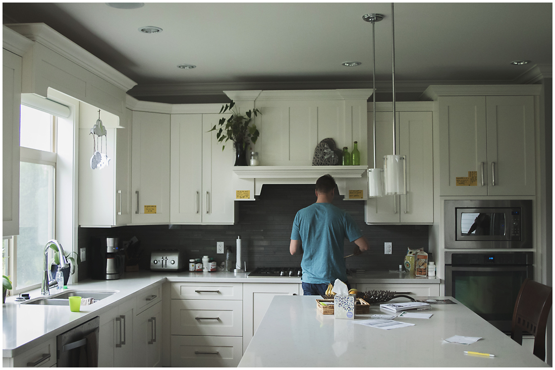 father working in white kitchen  #documentaryphotography #lifestlyephotography #vancouver #langley #fraservalley #mother #father #kids #trampoline #jenga #booknook #lifestyle #inhome #fall #familyof5 #fourthbaby #maternity #reading #whitekitchen #activefathers #playwithyourkids