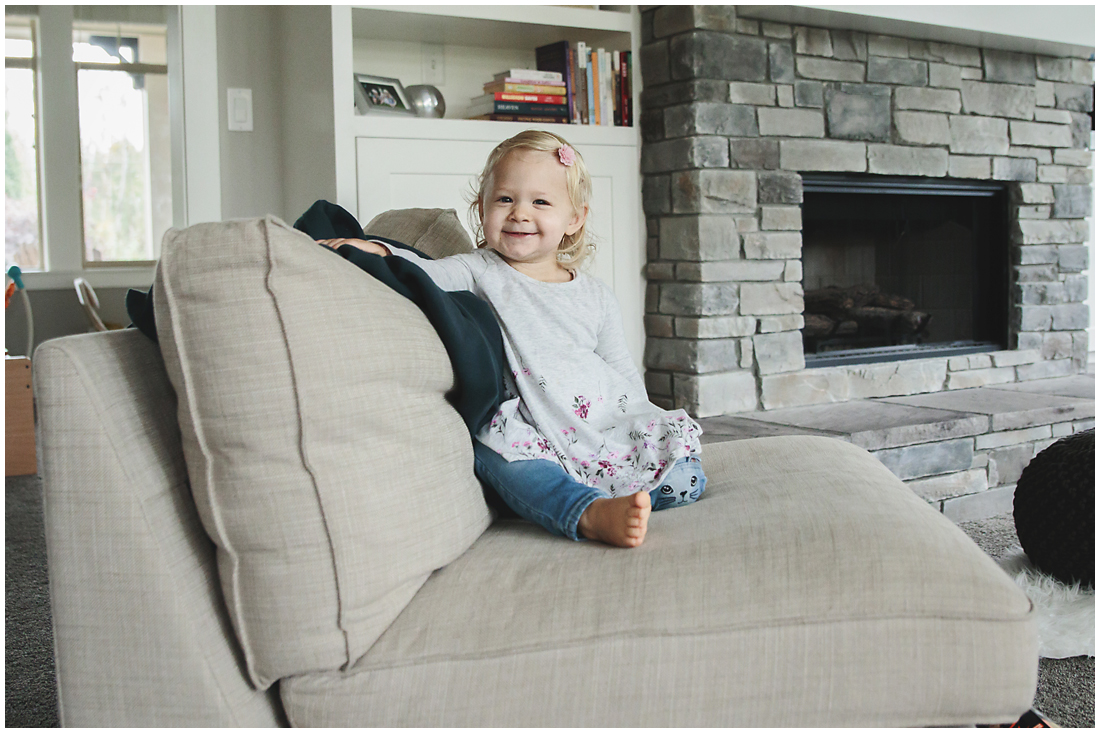 toddler girl sitting by fireplace during in home documentary maternity session