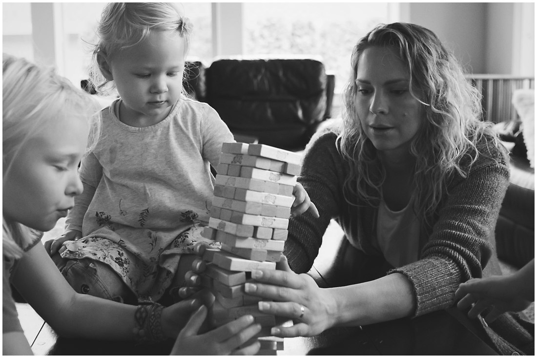 jenga tower falling over during family game  #documentaryphotography #lifestlyephotography #vancouver #langley #fraservalley #mother #father #kids #trampoline #jenga #booknook #lifestyle #inhome #fall #familyof5 #fourthbaby #maternity #reading #whitekitchen #activefathers #playwithyourkids