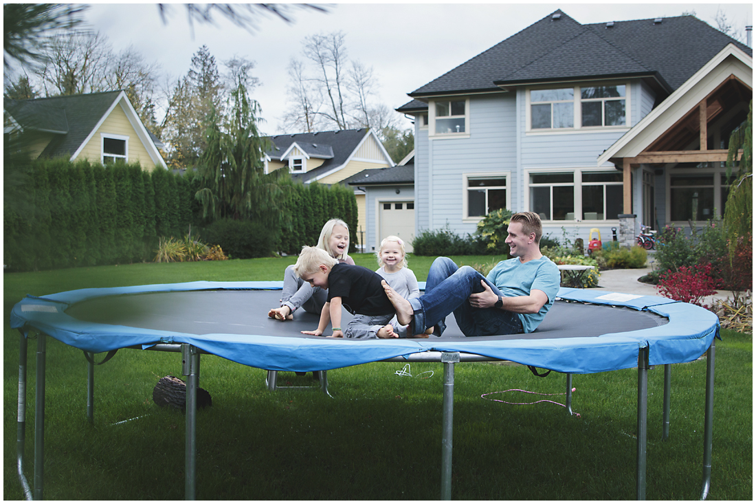 father and children playing on trampoline laughing in back yard  #documentaryphotography #lifestlyephotography #vancouver #langley #fraservalley #mother #father #kids #trampoline #jenga #booknook #lifestyle #inhome #fall #familyof5 #fourthbaby #maternity #reading #whitekitchen #activefathers #playwithyourkids