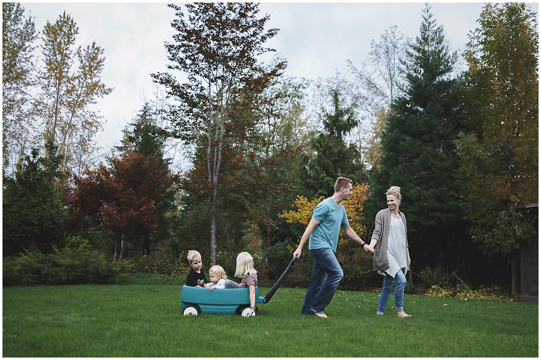 three children being pulled in wagon by mum and dad  #documentaryphotography #lifestlyephotography #vancouver #langley #fraservalley #mother #father #kids #trampoline #jenga #booknook #lifestyle #inhome #fall #familyof5 #fourthbaby #maternity #reading #whitekitchen #activefathers #playwithyourkids