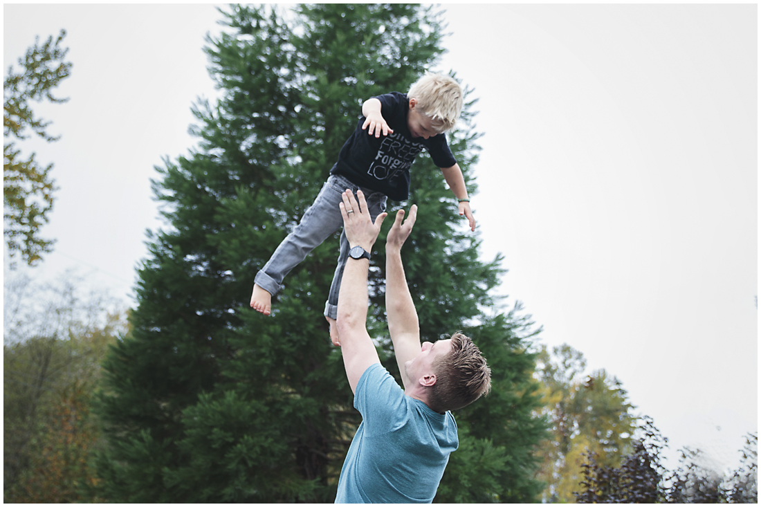 father throwing son into the air  #documentaryphotography #lifestlyephotography #vancouver #langley #fraservalley #mother #father #kids #trampoline #jenga #booknook #lifestyle #inhome #fall #familyof5 #fourthbaby #maternity #reading #whitekitchen #activefathers #playwithyourkids