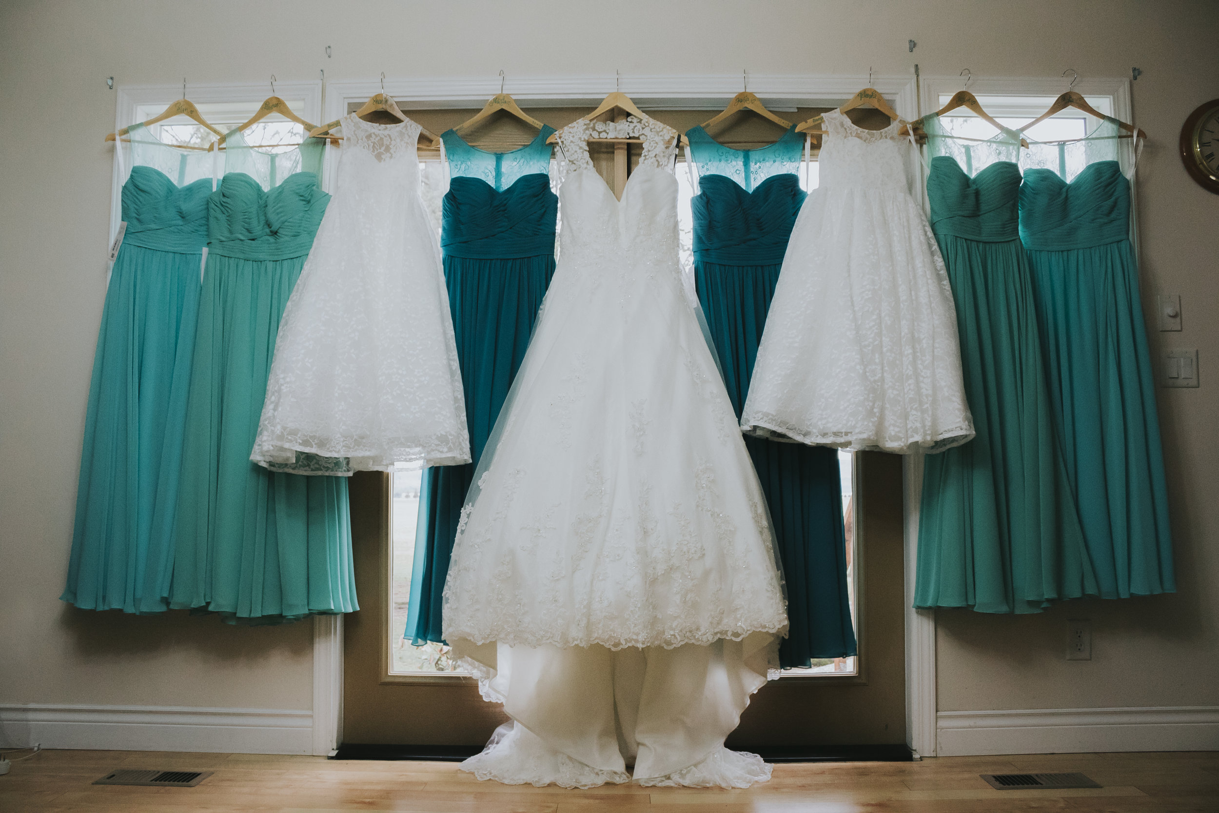 Wedding dress and bridesmaids dresses hanging. A rainy forest wedding in Lynden Washington, featuring teal blue accents, rustic details, umbrellas and a large bridal party.  #rain #wedding #lynden  #washington #umbrella #spring #teal #grey #brown #trees #romantic #documentarywedding #unposed #romanticposes #couple #largebridalparty   Photography by Christina Voorhorst of Mimsical Photography. Do not alter, crop, edit or share these images without proper credit or permission. www.mimsicalphotography.com