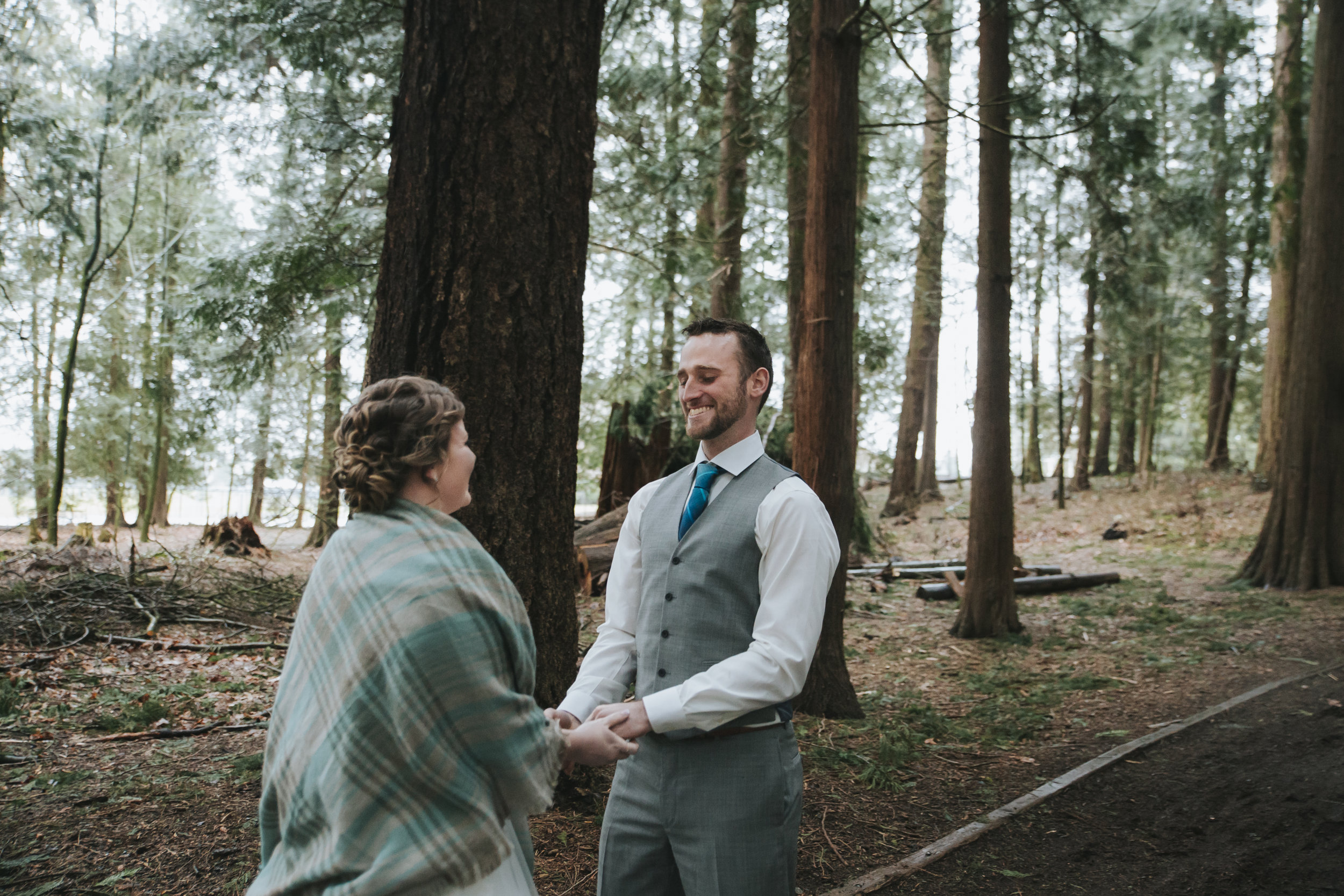 First look    A rainy forest wedding in Lynden Washington, featuring teal blue accents, rustic details, umbrellas and a large bridal party.#rain #wedding #lynden  #washington #umbrella #spring #teal #grey #brown #trees #romantic #documentarywedding #unposed #romanticposes #couple #largebridalparty   Photography by Christina Voorhorst of Mimsical Photography. Do not alter, crop, edit or share these images without proper credit or permission. www.mimsicalphotography.com