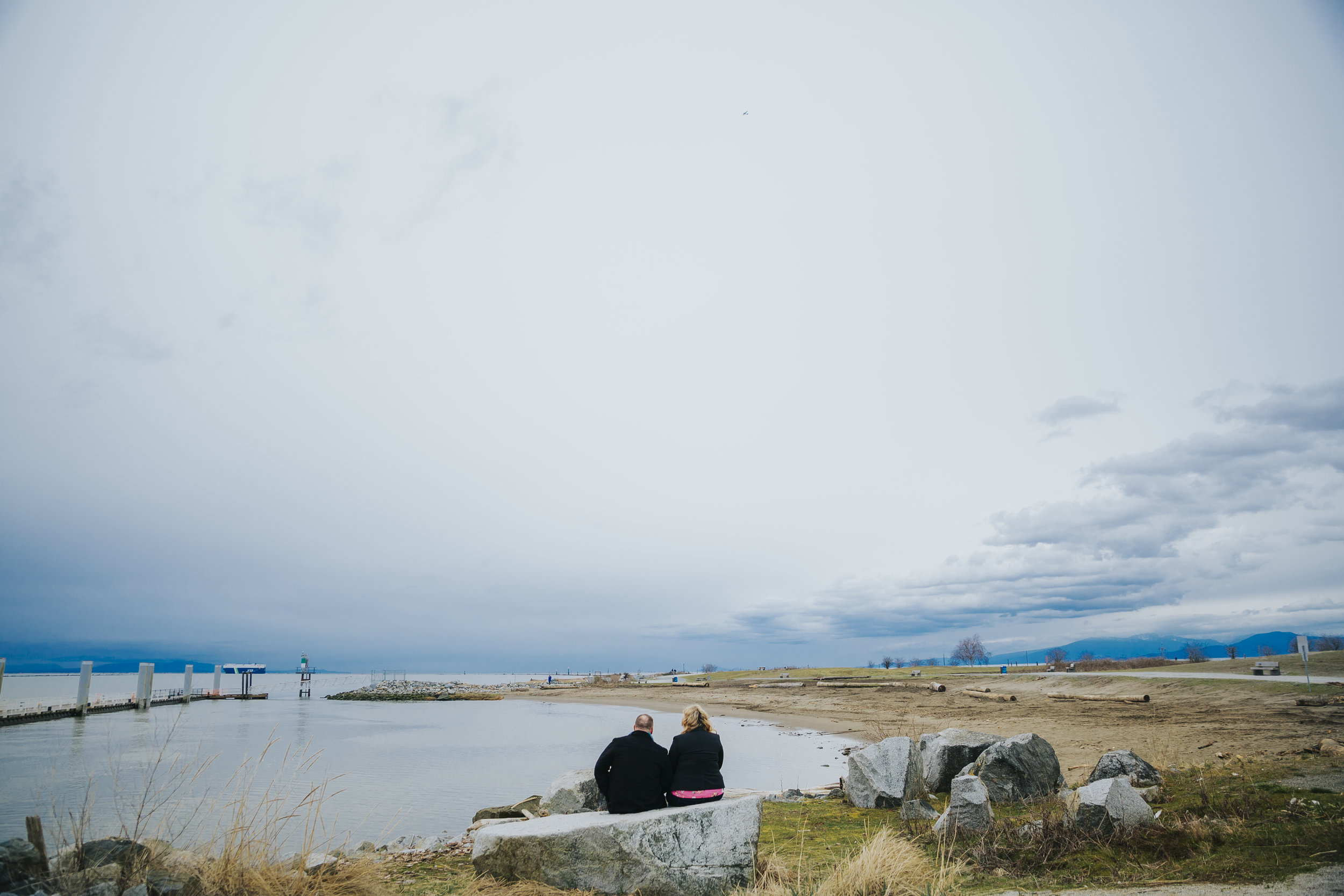 Cloudy engagement session at Garry Point Park in Richmond, BC. Couple sitting on rock  Photography by Christina Voorhorst of Mimsical Photography  #westcoastphotographer #engagement #ring #couple #ocean #cloud #overcast #romantic #poses