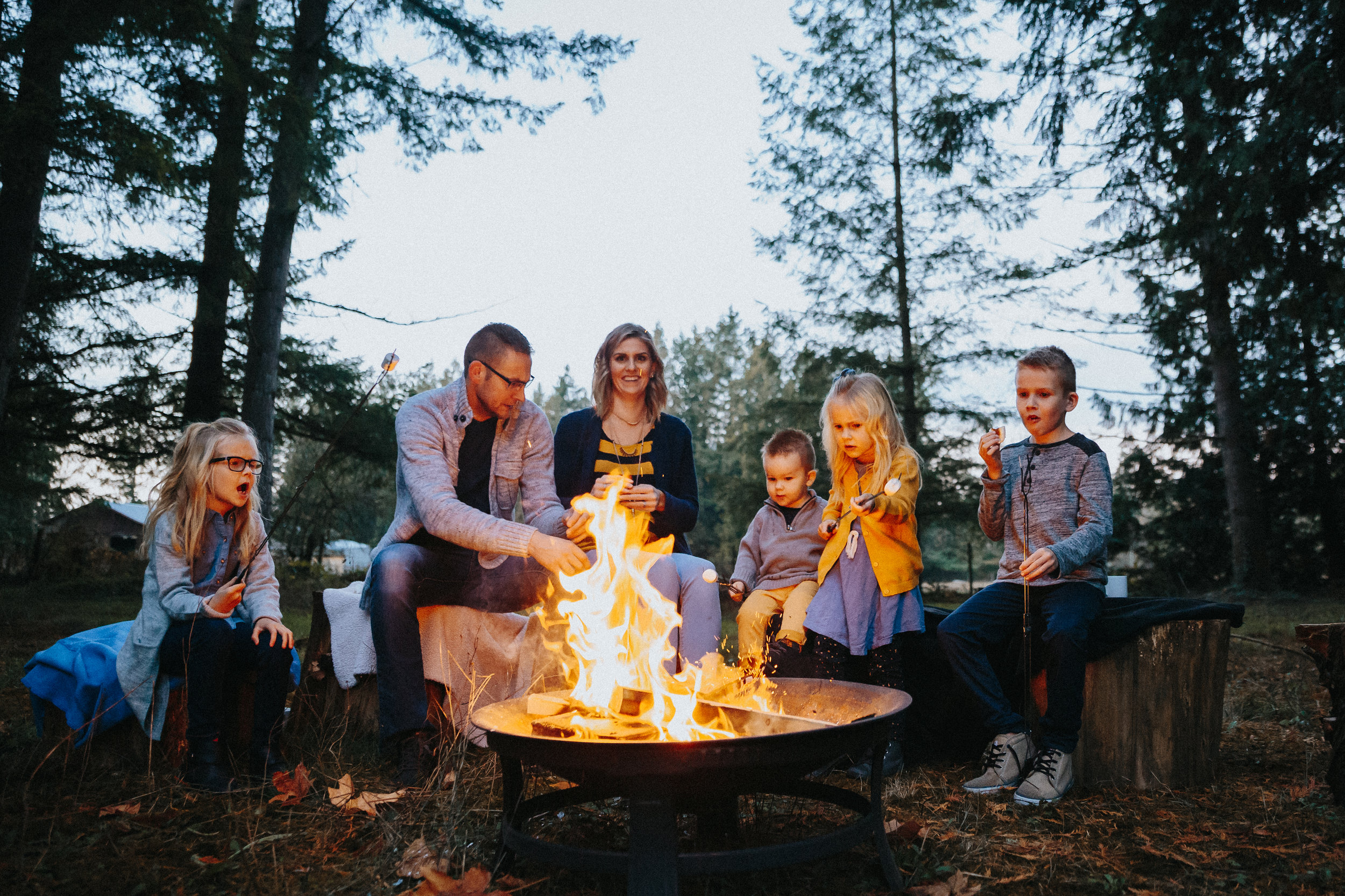 Family of 6 sitting around the fire, large family.Backyard Family Roasting Marshmallows, 4 kids, navy blue, mustard yellow, jean . Real moments, real memories. sticky fingers, documentary lifestyle photography by Mimsical photography, Fraser Valley, British Columbia, Langley, Vancouver.