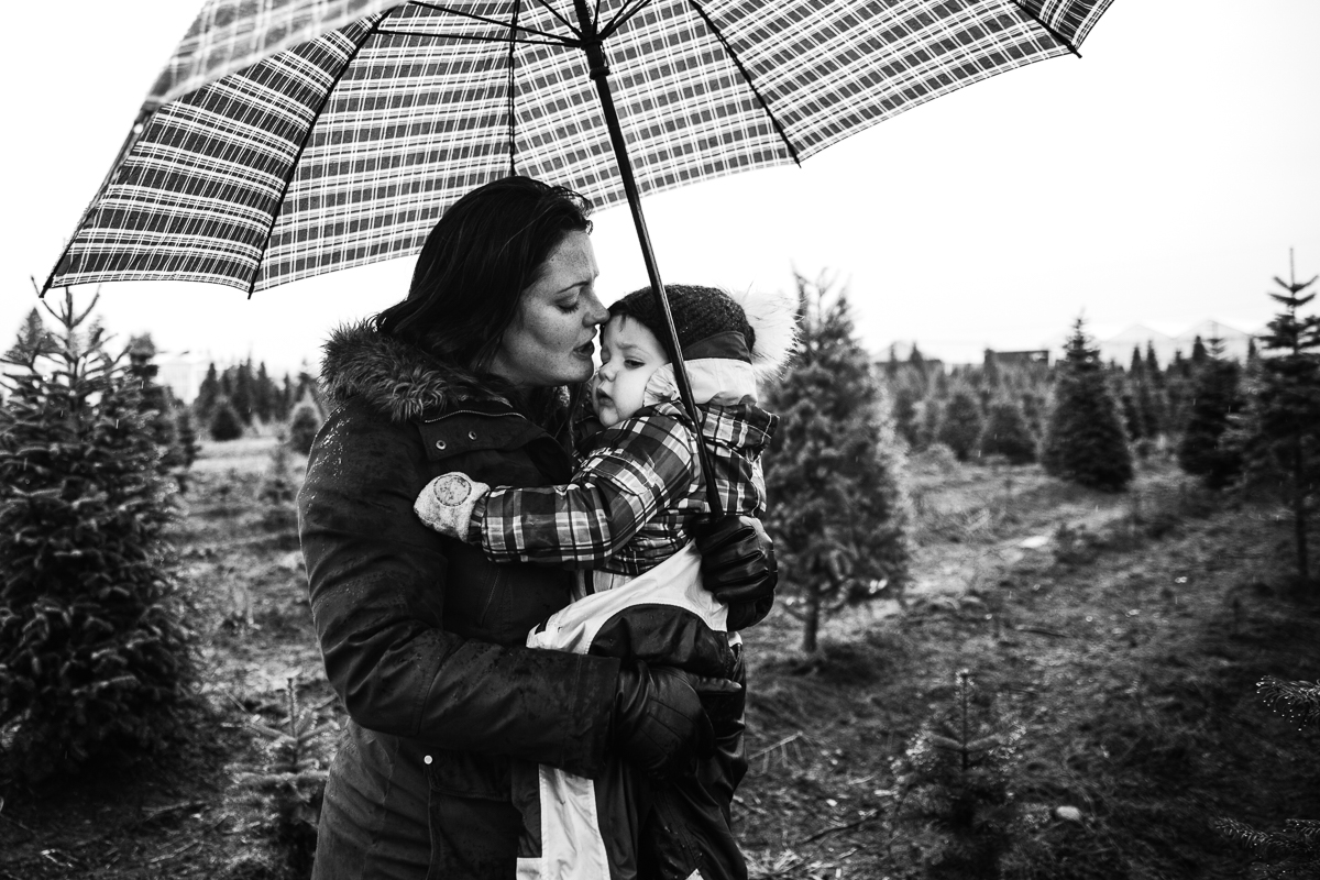 Snuggles with mum under the umbrella   Christmas Tree Hunt Tradition at Oh Christmas Tree Farms in Langley, BC. Documentary Family Holiday Tradition, Real life moments with a family of 7 by Mimsical Photography. West Coast photographer in Lower Mainland, British Columbia