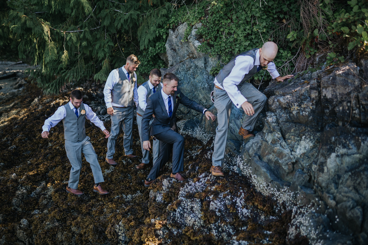groomsmen climbing over rocks in light grey and groom in dark grey suit  photo credit: karin louwerse edit: mimsical photography  Mimsical Photography Documentary Wedding Photography, Camp Howdy, Belcarra Provincial Park, North Vancouver. Purple and Grey Wedding Colours, Natural Greenery, Rustic Details, Summer, Lace and chiffon, big wedding, greek, lower mainland, british columbia, real, genuine, candid