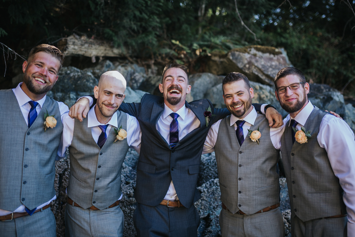 groomsmen laughing with groom in group hug - light grey vest and purple ties. orange rose boutinere   Mimsical Photography Documentary Wedding Photography, Camp Howdy, Belcarra Provincial Park, North Vancouver. Purple and Grey Wedding Colours, Natural Greenery, Rustic Details, Summer, Lace and chiffon, big wedding, greek, lower mainland, british columbia, real, genuine, candid