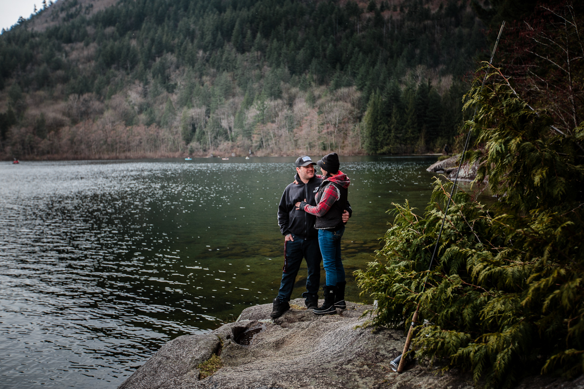Man wearing black hoodie and black baseball cap hugging woman in plaid sweater and black vest wearing a black toque while standing on a rock overlooking a perfectly clear lake surrounded by mountains Sasquatch Park Hicks Lake Camping Engagement Session Plaid Fishing Child Forest Fun Candid Documentary-150.JPG