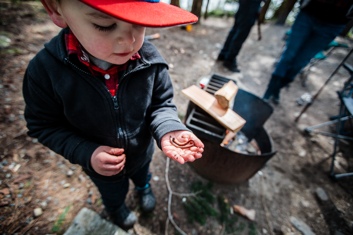 little boy holding worm in his hand by a campfire while camping at Sasquatch Park Hicks Lake Camping Engagement Session Plaid Fishing Child Forest Fun Candid Documentary-110.JPG