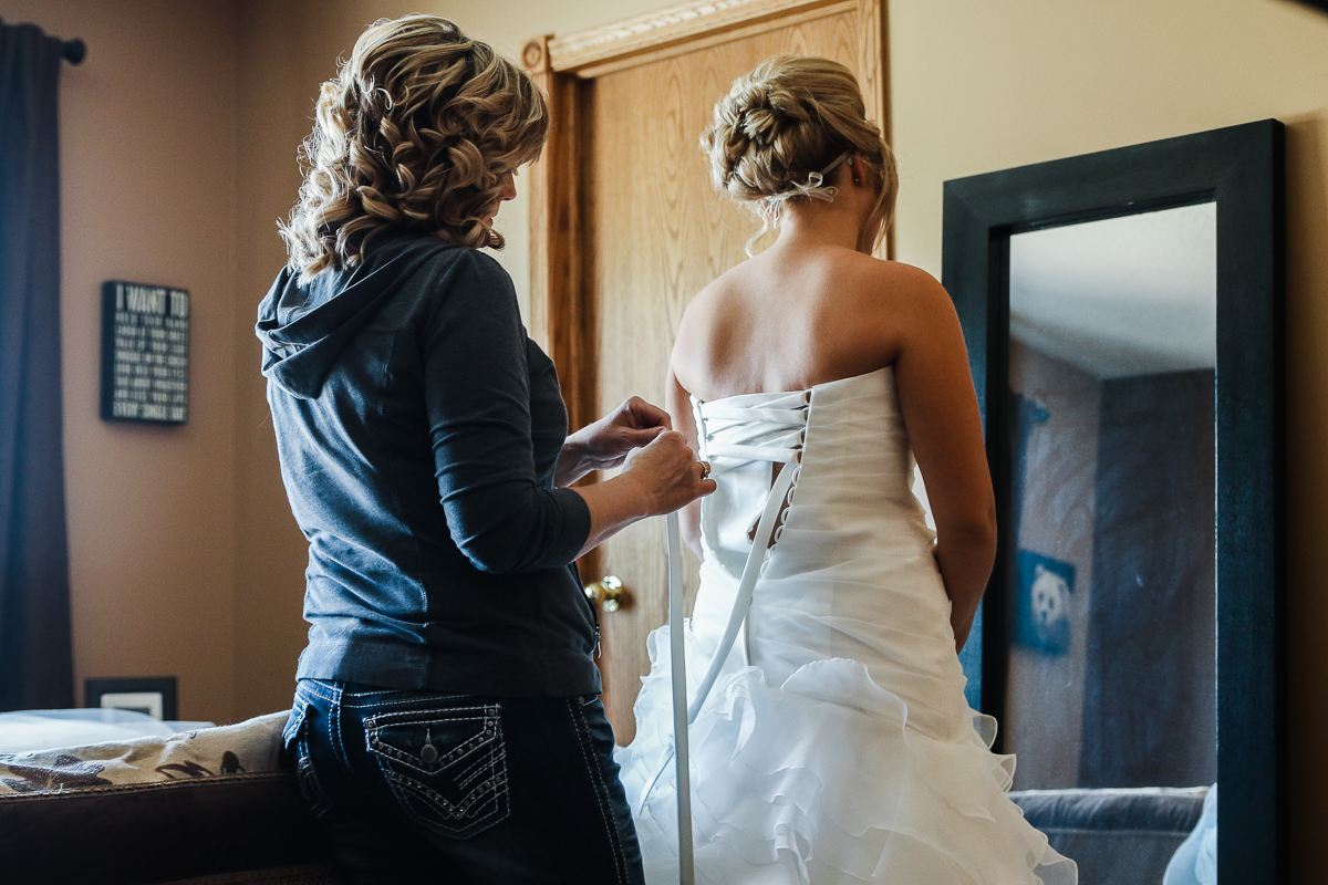 Mother of the bride lacing up her daughter in a corset back wedding dress facing a mirror in a country wedding in lethbridge, alberta