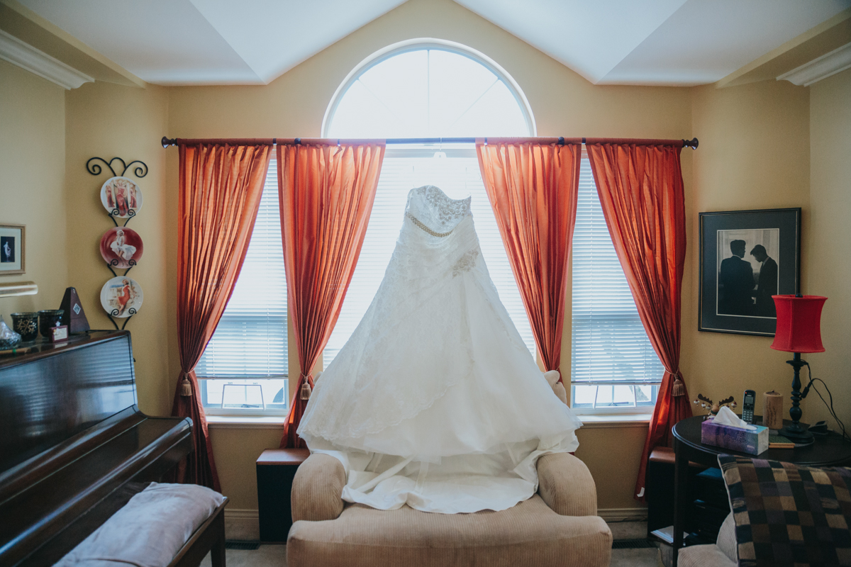 Wedding dress hanging in the window of a family home in Delta, British Columbia. Pregnant Bride East Delta Hall Wedding