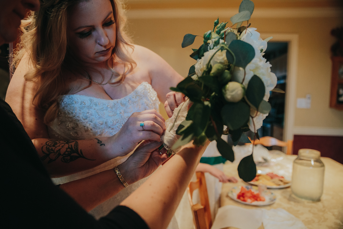 Bride in dress wrapping her boquet in a heirloom handkerchief as her something old and sentimental for her wedding