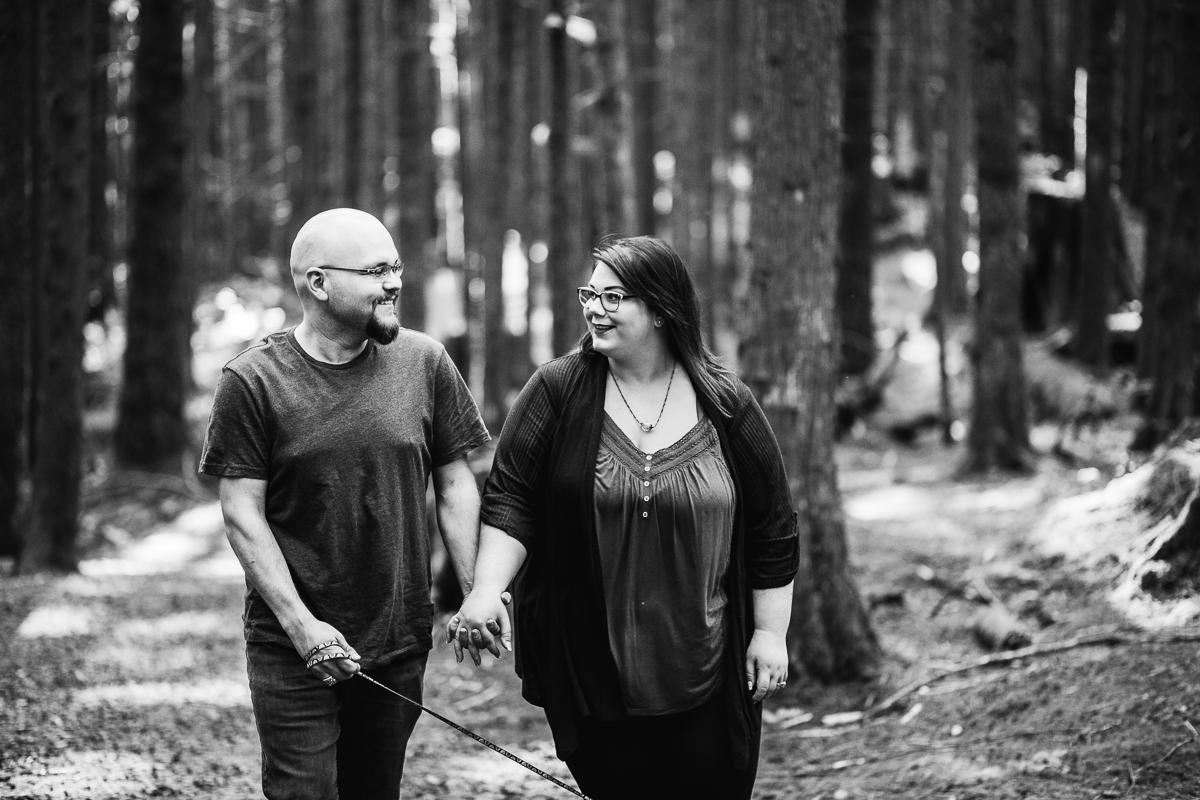 Couple looking at each other smiling while walking and holding hands during spring engagement photography at  Spirea Nature Trail in Golden Ears Provincial Park in British Columbia by Mimsical Photography