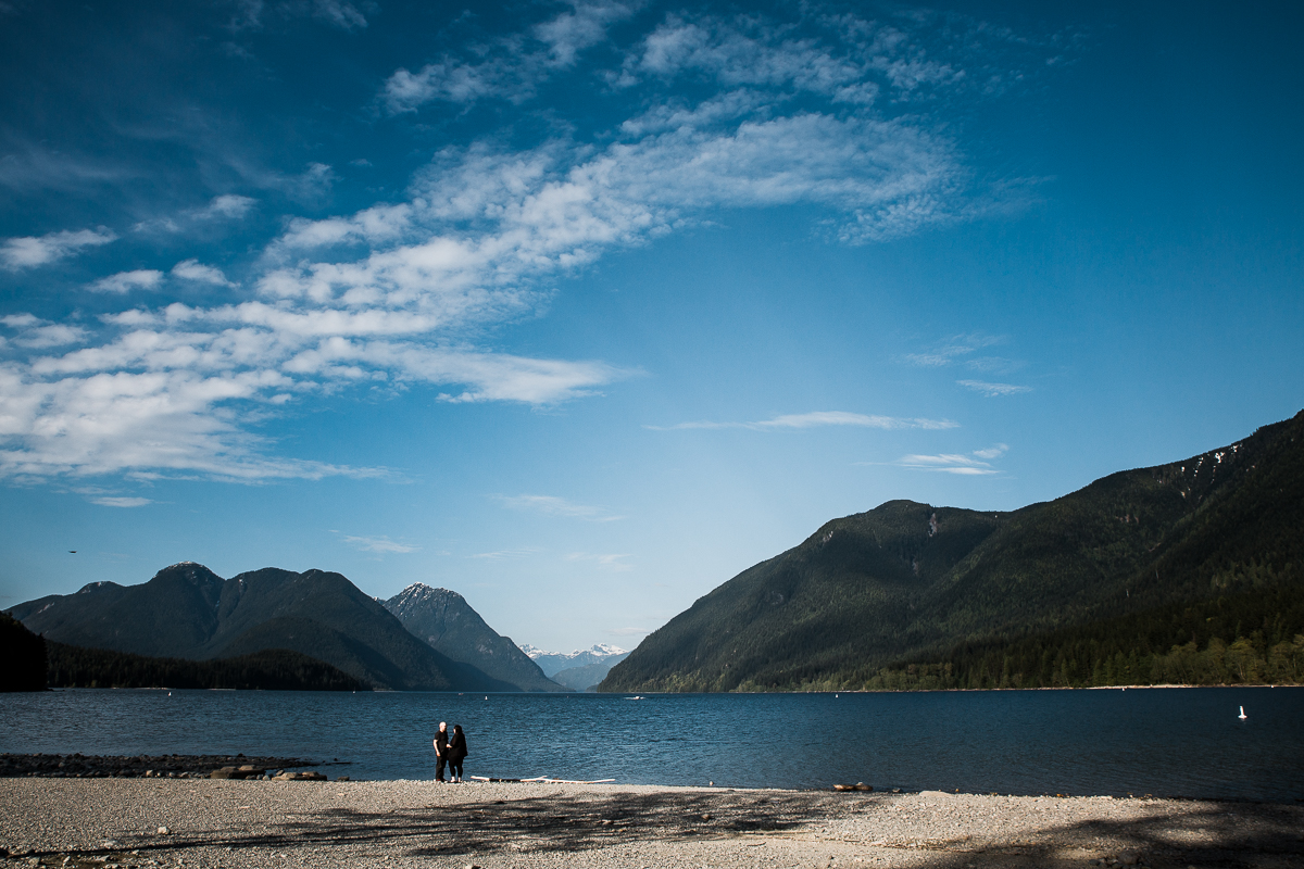 Rich colours of a evening overlooking Alouette Lake from the beach on the south end of the lake looking northward couple holding hands during spring engagement photography at  Alouette Lake in  Golden Ears Provincial Park in British Columbia by Mimsical Photography
