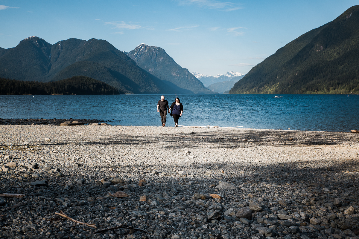 Couple walking down rocky beach overlooking the mountains of Alouette Lake during spring engagement photography at  Alouette Lake in  Golden Ears Provincial Park in British Columbia by Mimsical Photography