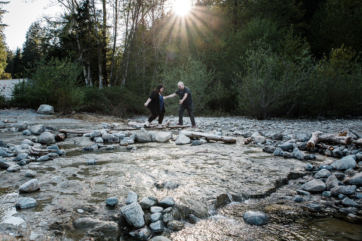 Man helping fiance across small beach river during spring engagement photography at  Alouette Lake in  Golden Ears Provincial Park in British Columbia by Mimsical Photography