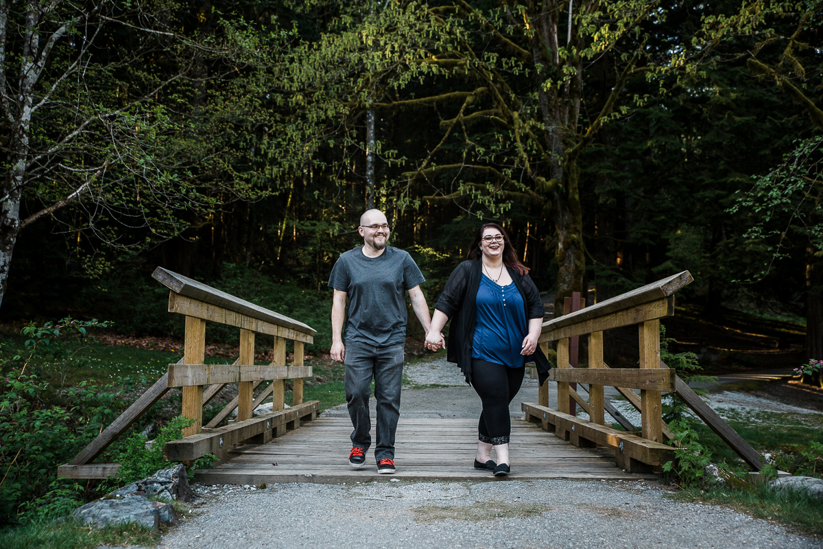 Couple walking across wooden bridge holding hands and laughing during spring engagement photography at  Alouette Lake in  Golden Ears Provincial Park in British Columbia by Mimsical Photography