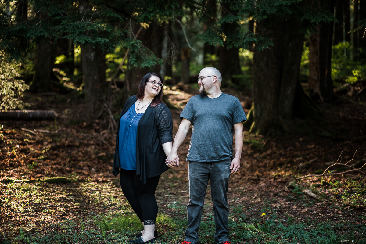 Couple holding hands wearing black legging blue shirt and grey jeans leaning away from each other while looking at each other couple pose plus size flattering poses during spring engagement photography at  Alouette Lake in  Golden Ears Provincial Park in British Columbia by Mimsical Photography
