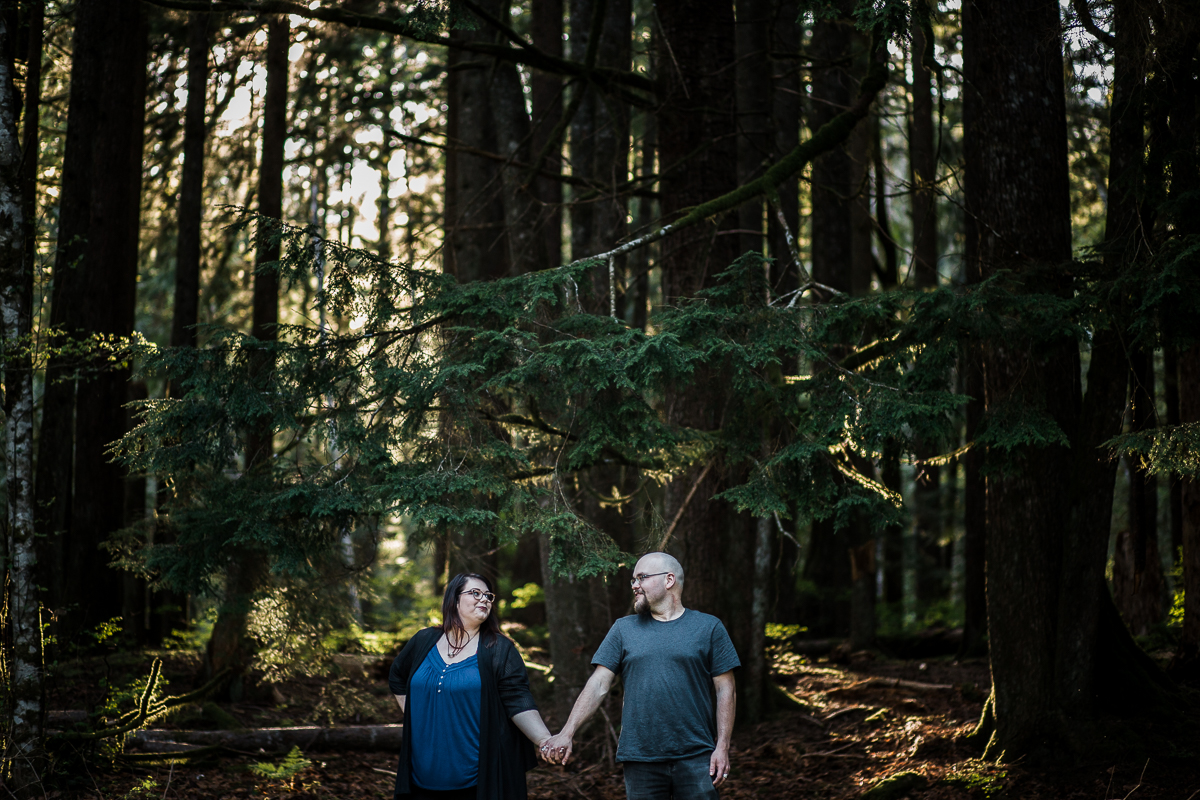 Engaged couple standing in forest holding hands and looking at each other during spring engagement photography at  Alouette Lake in  Golden Ears Provincial Park in British Columbia by Mimsical Photography
