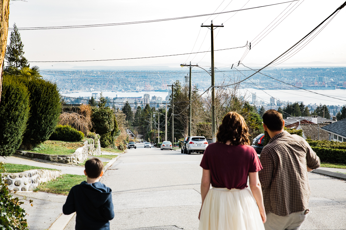 Girl wearing maroon shirt and white tulle skirt holding hands with a beared man wearing plaid walking down hill overlooking Vancouver residential side street during their engagement photography session with Mimsical Photography in their backyard forest on the side of north vancouver mountain on a sunny day.