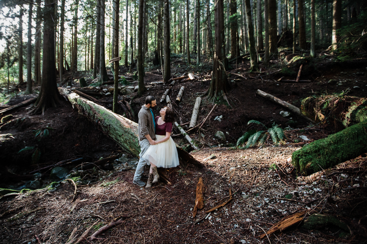 Girl in white tutu sitting on tree log looking up at her fiance in romantic pose during their engagement photography session with Mimsical Photography in their backyard forest on the side of north vancouver mountain on a sunny day.
