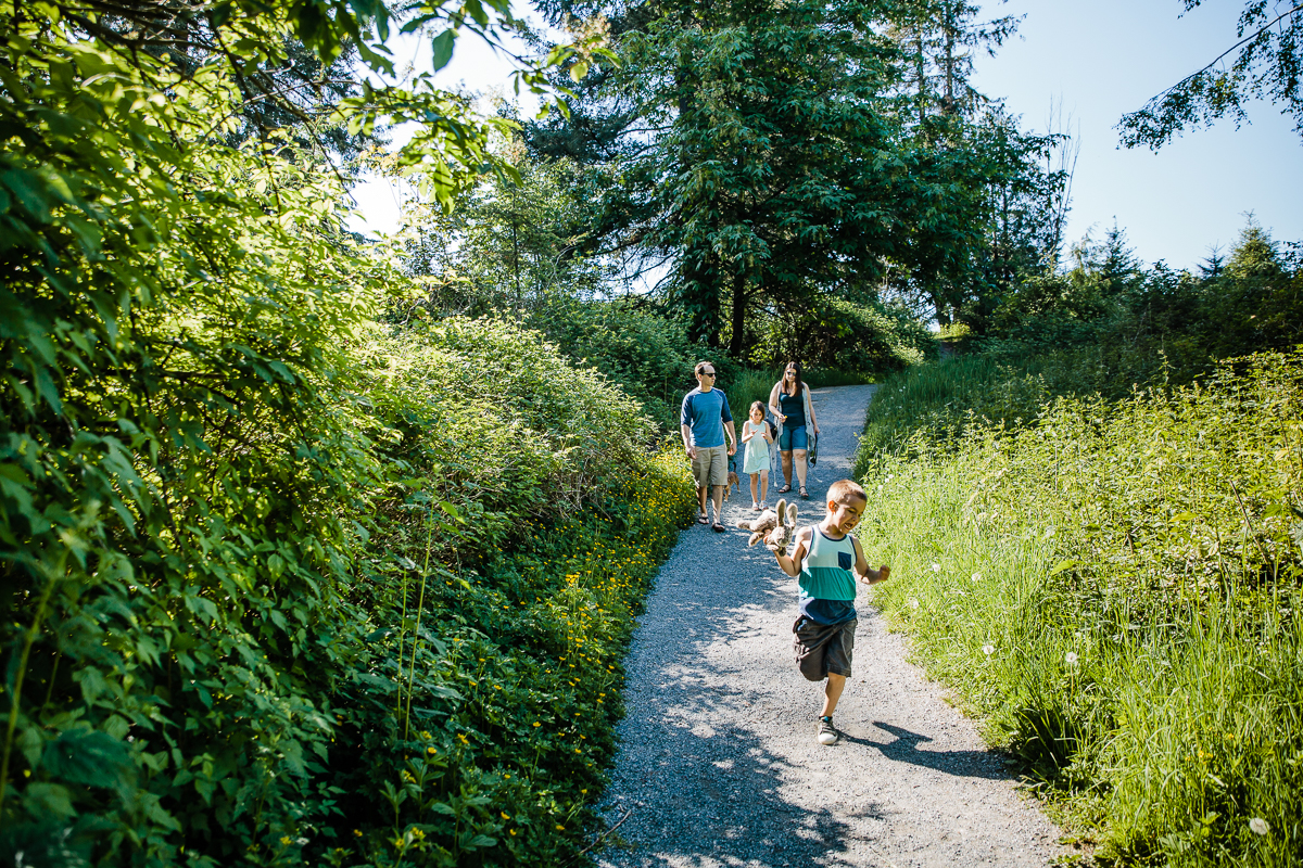 Little boy holding stuffed bunny running down gravel path in front of family walking during a Family Photography session at Aldergrove Bowl Provincial park in Abbotsford, British Columbia on a spring day  #vancouverfamilyphotographer #metrovancouver #candidfamilyphotos #lifestylefamily by mimsical photography christina voorhorst