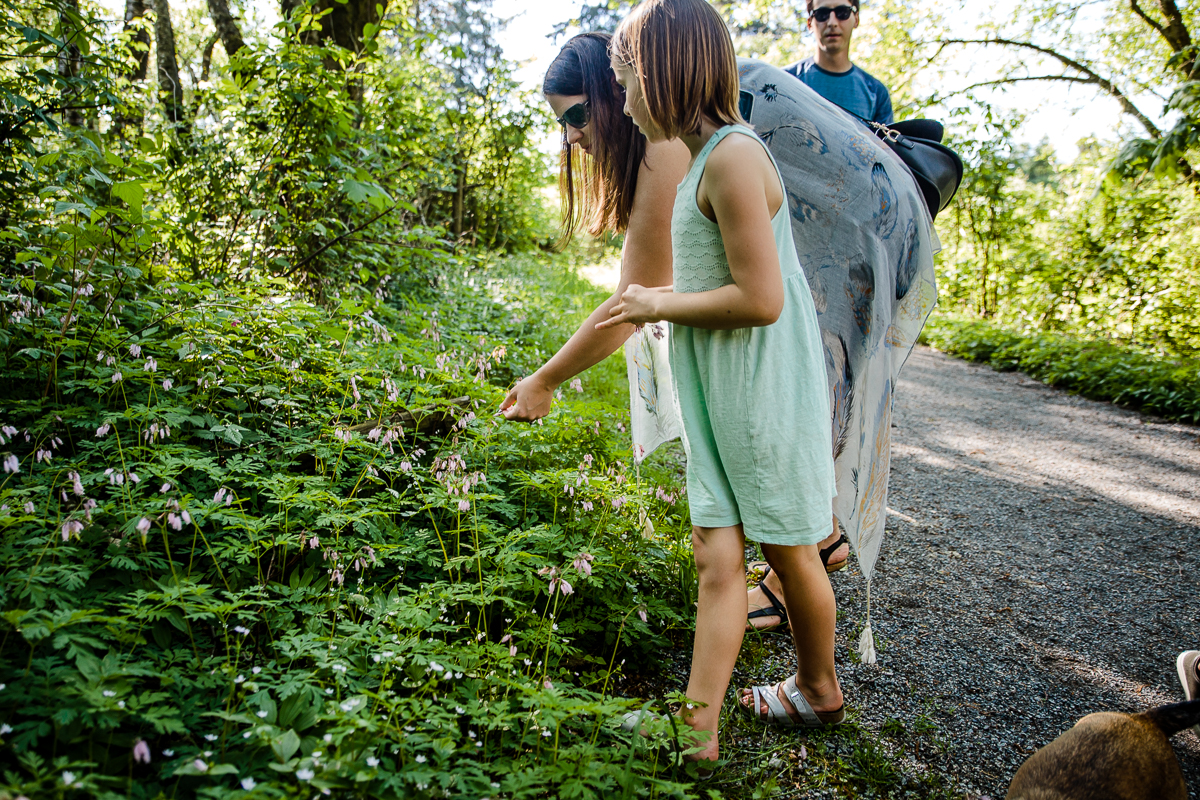 Mother looking at forest wildflowers with daughter wearing a teal summer dress during a Family Photography session at Aldergrove Bowl Provincial park in Abbotsford, British Columbia on a spring day  #vancouverfamilyphotographer #metrovancouver #candidfamilyphotos #lifestylefamily by mimsical photography christina voorhorst