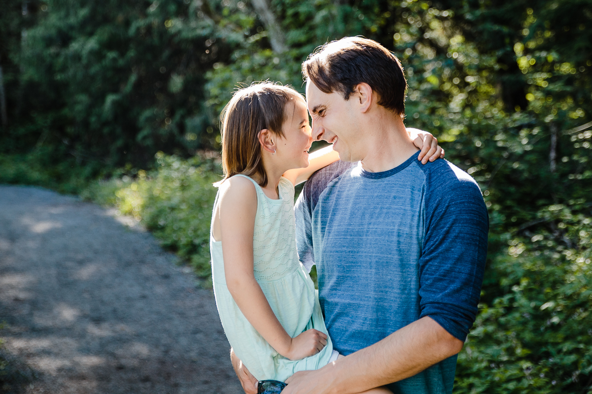 Father carrying daughter and giving her nose rub butterfly kisses in a tender moment  during a Family Photography session at Aldergrove Bowl Provincial park in Abbotsford, British Columbia on a spring day  #vancouverfamilyphotographer #metrovancouver #candidfamilyphotos #lifestylefamily by mimsical photography christina voorhorst