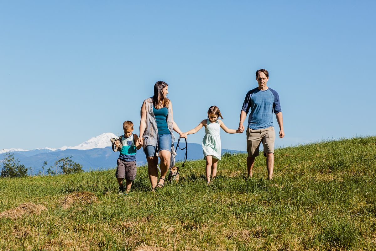 Family of four walking through field with Mount Baker in the background during a Family Photography session at Aldergrove Bowl Provincial park in Abbotsford, British Columbia on a spring day  #vancouverfamilyphotographer #metrovancouver #candidfamilyphotos #lifestylefamily by mimsical photography christina voorhorst