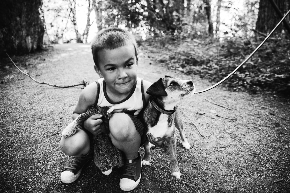 Young boy holding stuffed rabbit and crouching down to hug small dog in black and white during a Family Photography session at Aldergrove Bowl Provincial park in Abbotsford, British Columbia on a spring day  #vancouverfamilyphotographer #metrovancouver #candidfamilyphotos #lifestylefamily by mimsical photography christina voorhorst
