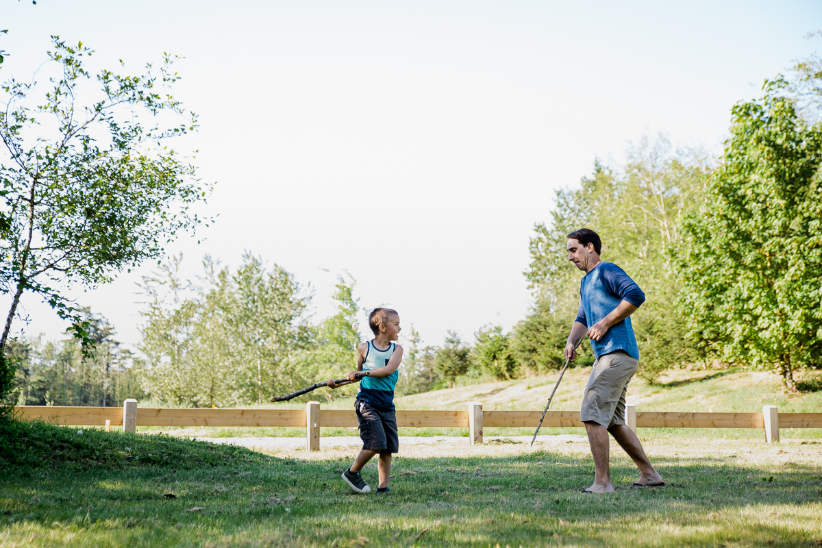 Father and son having a stick sword fight in the shade on a sunny day during a Family Photography session at Aldergrove Bowl Provincial park in Abbotsford, British Columbia on a spring day  #vancouverfamilyphotographer #metrovancouver #candidfamilyphotos #lifestylefamily by mimsical photography christina voorhorst