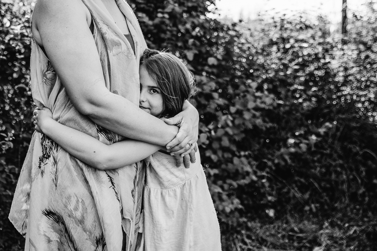 daughter hugging her mom's waist while looking at the camera during a Family Photography session at Aldergrove Bowl Provincial park in Abbotsford, British Columbia on a spring day  #vancouverfamilyphotographer #metrovancouver #candidfamilyphotos #lifestylefamily by mimsical photography christina voorhorst