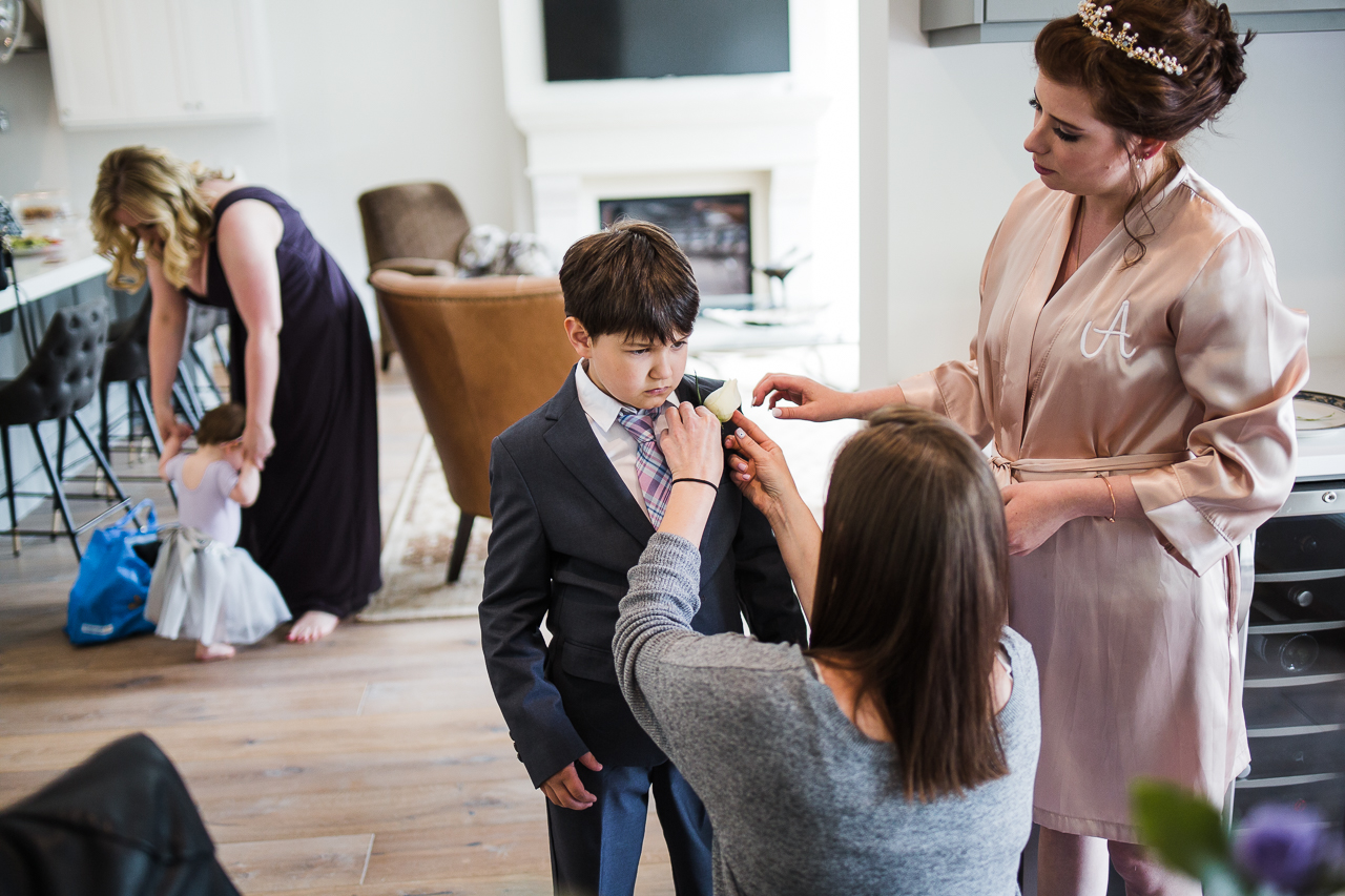 bride and sister pinning on buttoniere to ring bearer before outdoor summer wedding at Kwomais Point Park in Ocean Park Surrey British Columbia by Mimsical Photography who is a wedding photographer from Langley, BC that has a candid and documentary fun style.