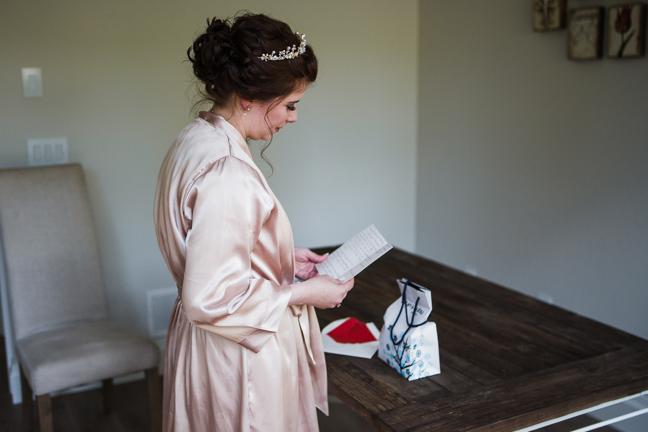 bride reading card from husband before wedding day before outdoor summer wedding at Kwomais Point Park in Ocean Park Surrey British Columbia by Mimsical Photography who is a wedding photographer from Langley, BC that has a candid and documentary fun style.