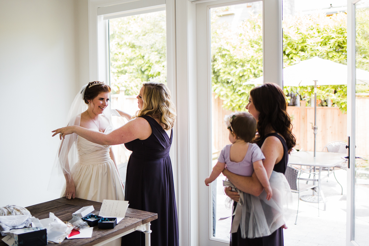 bridesmaids looking at bride when she is all ready before outdoor summer wedding at Kwomais Point Park in Ocean Park Surrey British Columbia by Mimsical Photography who is a wedding photographer from Langley, BC that has a candid and documentary fun style.