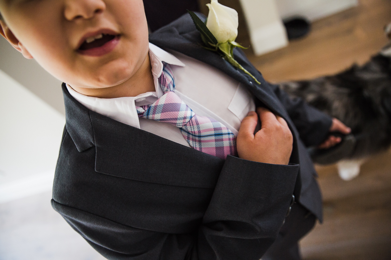 ring bearer checking security of rings in his suit pocket before outdoor summer wedding at Kwomais Point Park in Ocean Park Surrey British Columbia by Mimsical Photography who is a wedding photographer from Langley, BC that has a candid and documentary fun style.
