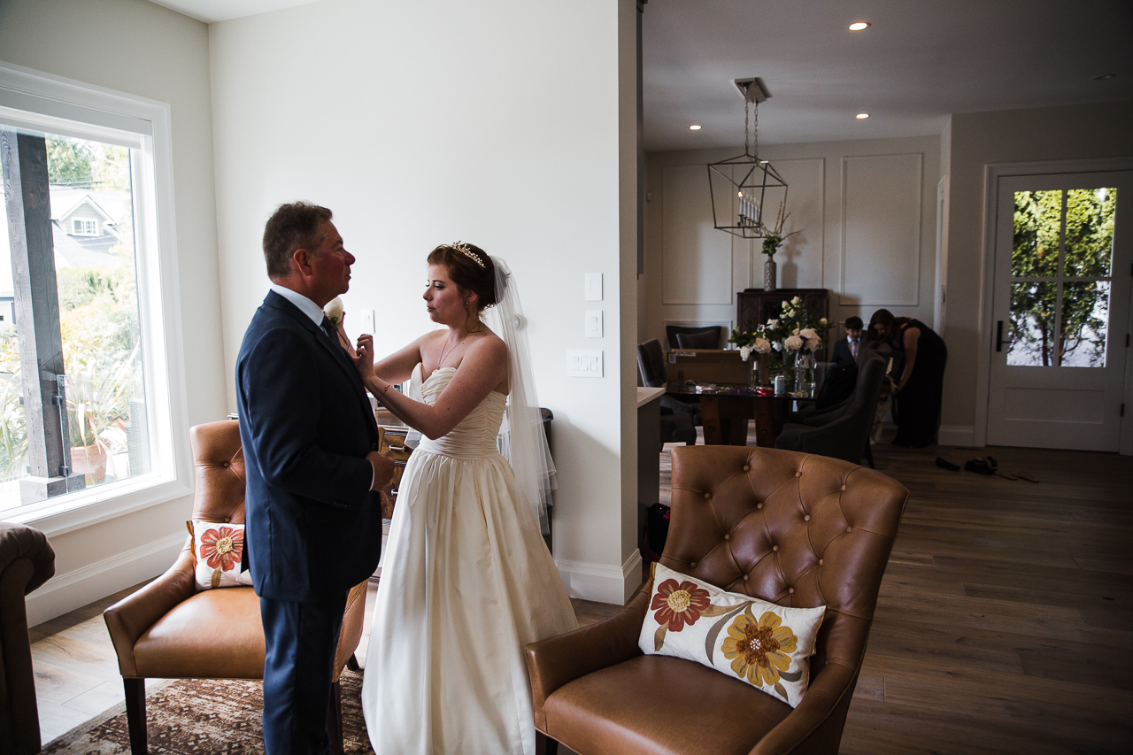 Bride pinning on the buttoniere to her father's suit in family home before outdoor summer wedding at Kwomais Point Park in Ocean Park Surrey British Columbia by Mimsical Photography who is a wedding photographer from Langley, BC that has a candid and documentary fun style.