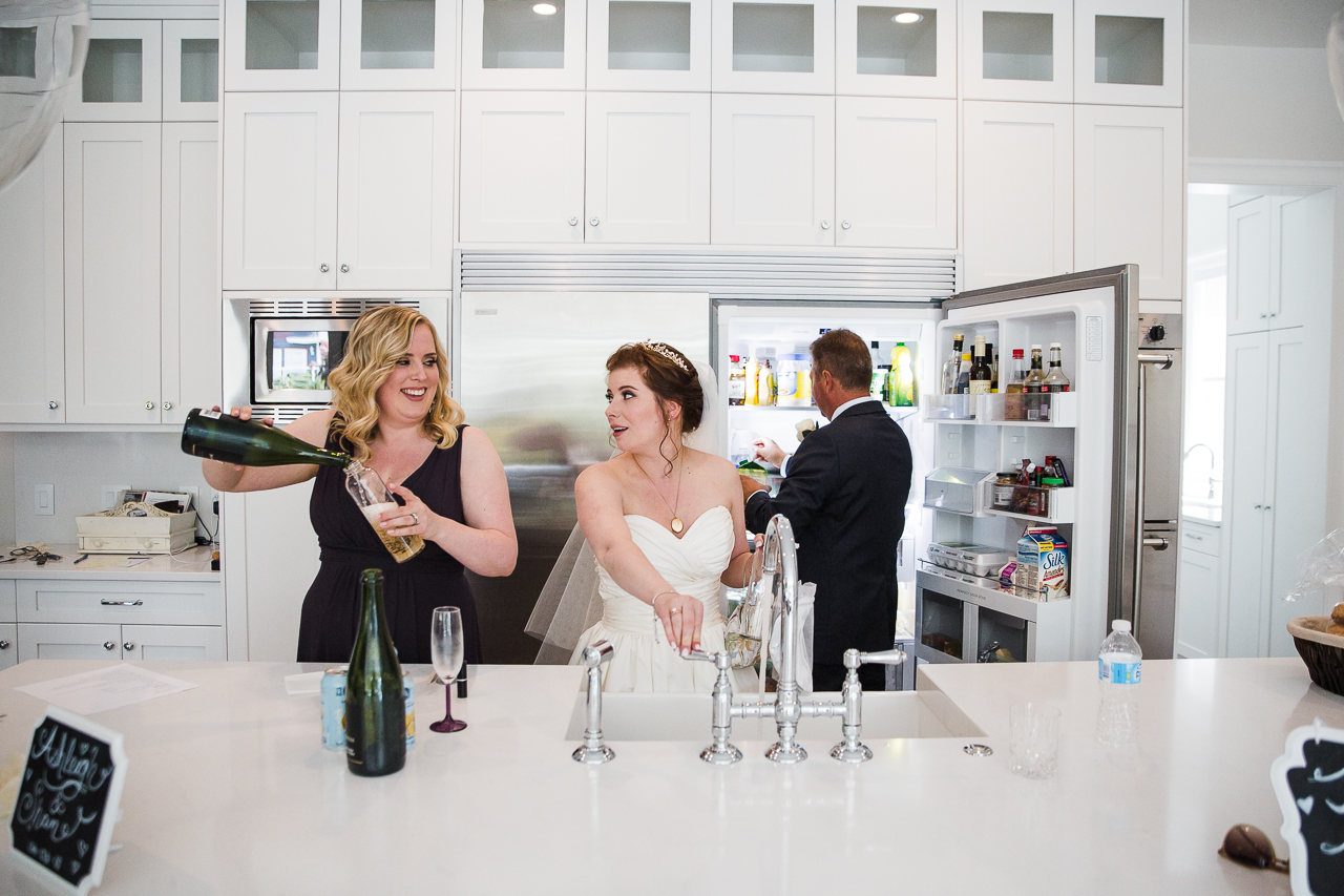 bride and maid of honour filling water bottles with water and champange in family kitchen before outdoor summer wedding at Kwomais Point Park in Ocean Park Surrey British Columbia by Mimsical Photography who is a wedding photographer from Langley, BC that has a candid and documentary fun style.