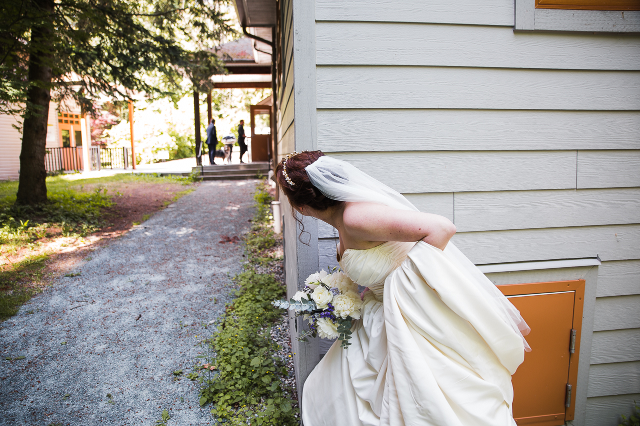 bride peeking around the corner of a building making sure guests don't see her before the ceremony before outdoor summer wedding at Kwomais Point Park in Ocean Park Surrey British Columbia by Mimsical Photography who is a wedding photographer from Langley, BC that has a candid and documentary fun style.