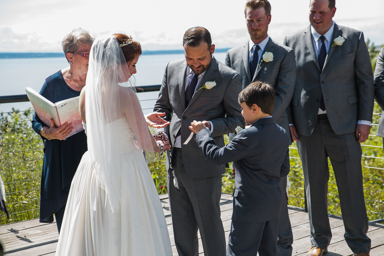 ringbearer handing the rings to his father during before outdoor summer wedding at Kwomais Point Park in Ocean Park Surrey British Columbia by Mimsical Photography who is a wedding photographer from Langley, BC that has a candid and documentary fun style.