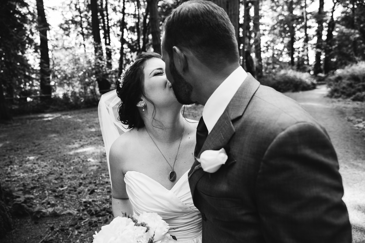 bride and groom kissing after outdoor summer wedding at Kwomais Point Park in Ocean Park Surrey British Columbia by Mimsical Photography who is a wedding photographer from Langley, BC that has a candid and documentary fun style.