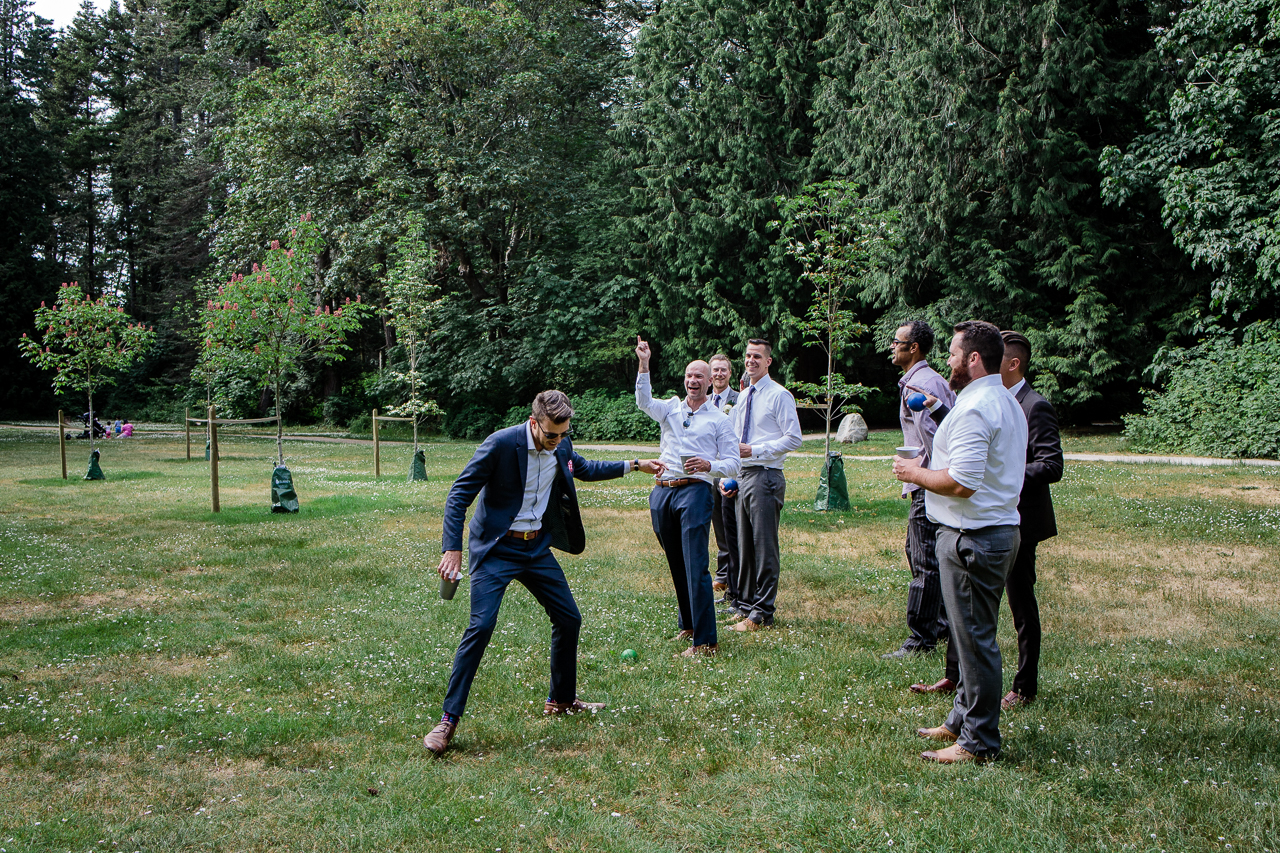 group of men playing boccie ball lawn game before wedding reception at Kwomais Hall by Kwomais Point Park in Ocean Park Surrey by best wedding photographer from Langley Mimsical Photography Christina Voorhorst style is documentary candid and fun photos