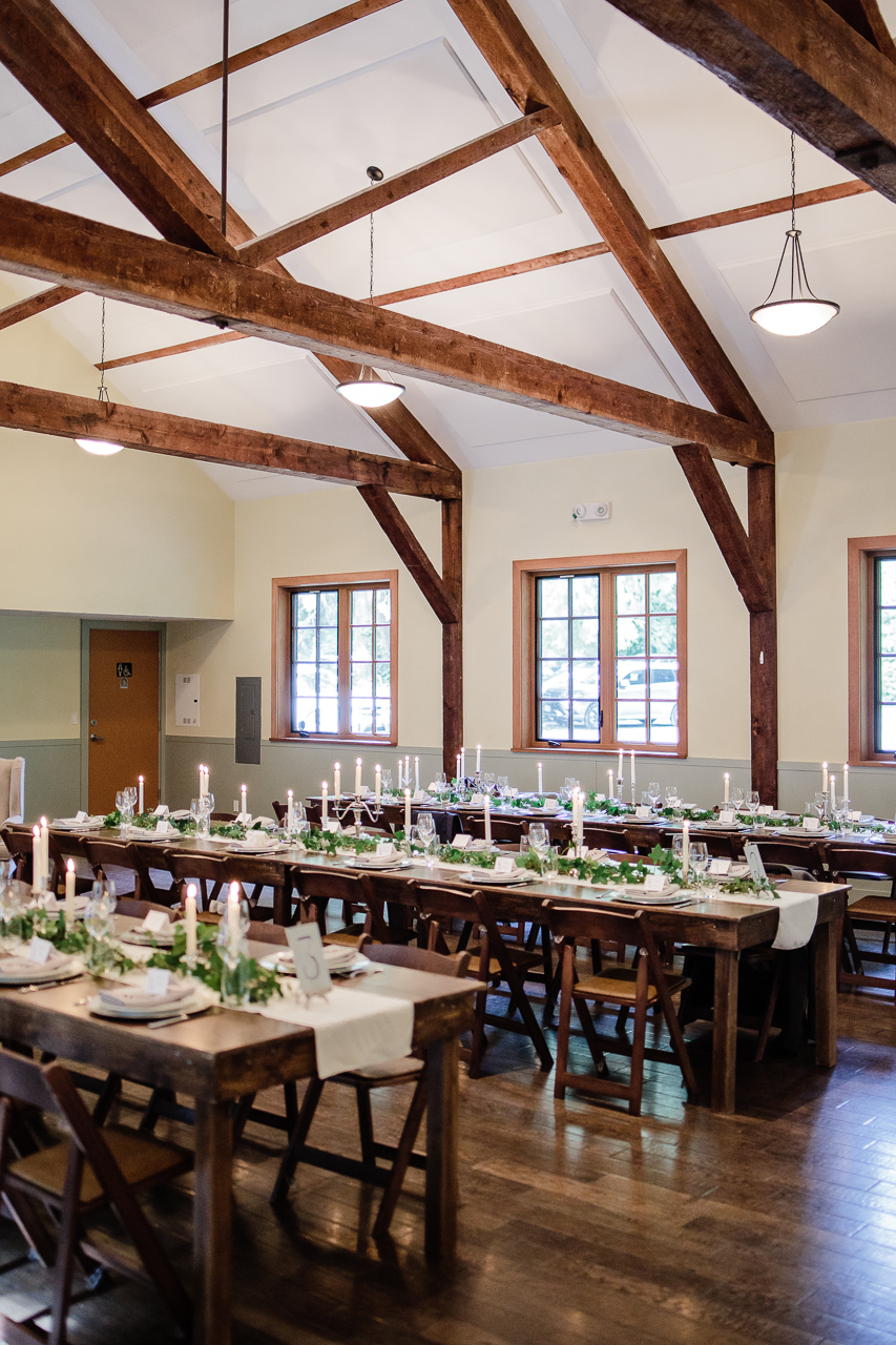 decorated long tables green real candles wooden fold up chairs before wedding reception at Kwomais Hall by Kwomais Point Park in Ocean Park Surrey by best wedding photographer from Langley Mimsical Photography Christina Voorhorst style is documentary candid and fun photos