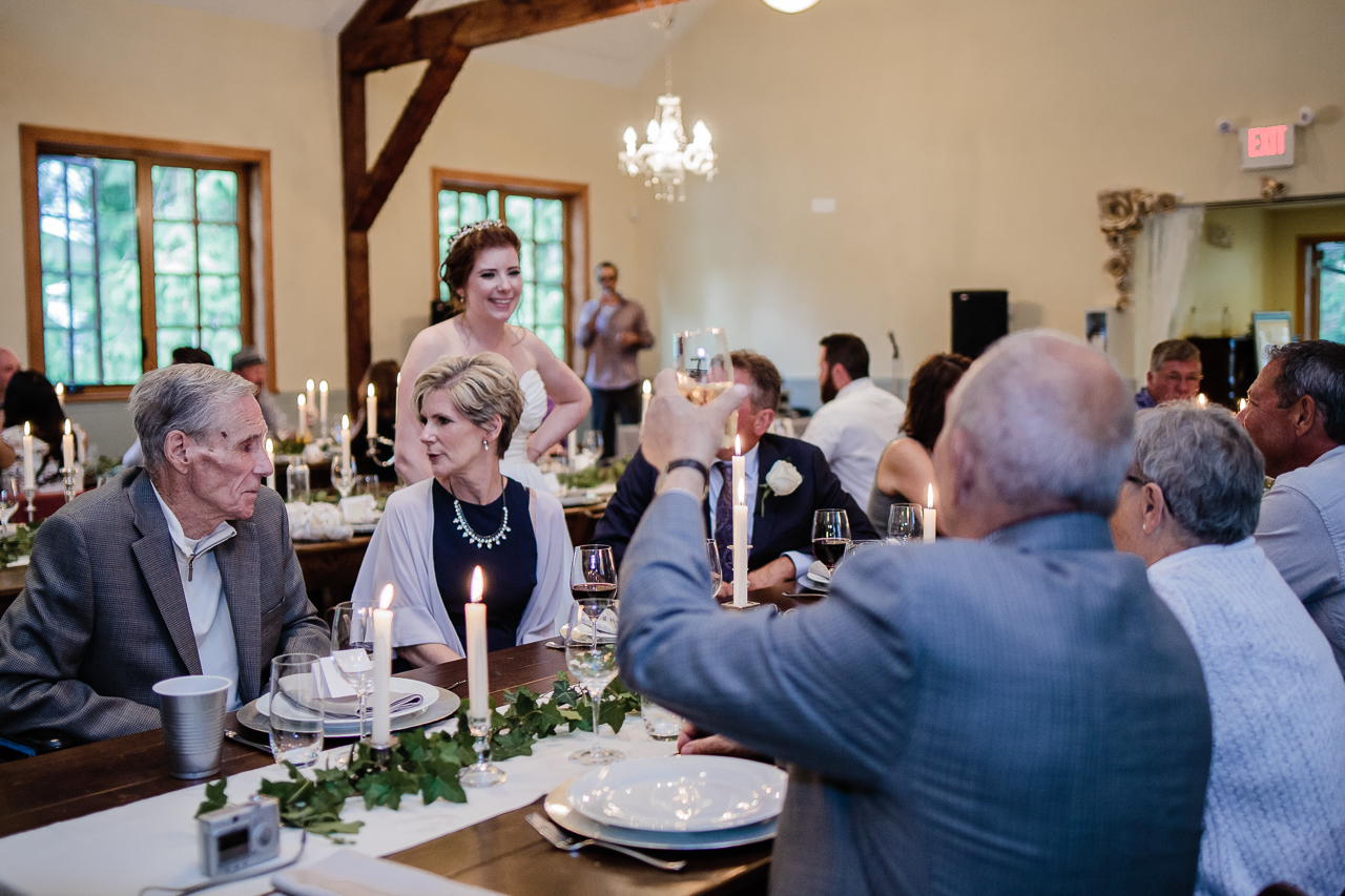 older man toasting the bride while sitting at table in rustic venue before wedding reception at Kwomais Hall by Kwomais Point Park in Ocean Park Surrey british columbia by best wedding photographer from Langley Mimsical Photography Christina Voorhorst style is documentary candid and fun photos
