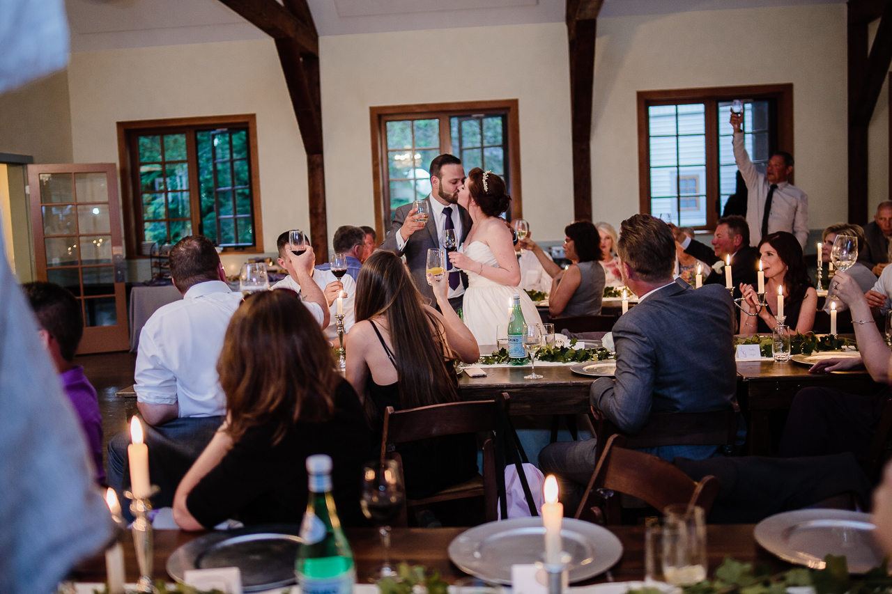 bride and groom kissing while family toasts them during rustic themed wedding reception at Kwomais Hall by Kwomais Point Park in Ocean Park Surrey british columbia by best wedding photographer from Langley Mimsical Photography Christina Voorhorst style is documentary candid and fun photos
